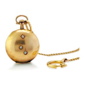 9. Zegarek kieszonkowy zdobiony motywem négligée z dewizką, pocz. XX w., Szwajcaria, Louis Grisel złoto 14 K, 3 szt. diamentów ł. ~ 0,10 ct, numer koperty: 150098, dewizka: złoto pr. 0,585, zapięcia złoto pr. 0,750; masa brutto: 34,86 g; wym. koperty: 3 x 4 cm.